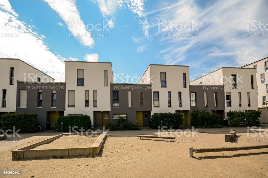 Moderne Stadthäuser in einem Wohngebiet, neue Wohnhäuser mit grünen Außenanlagen in der Stadt – Foto