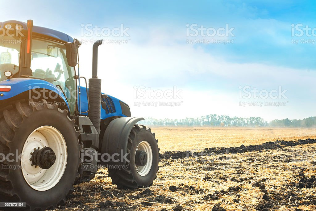 Modern tractor working in a field. stock photo