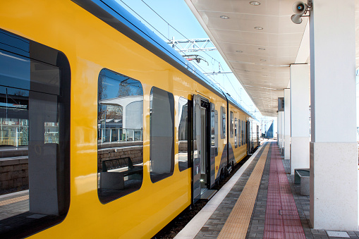 Beautiful yellow train at a station in Europe. The platform goes into perspective