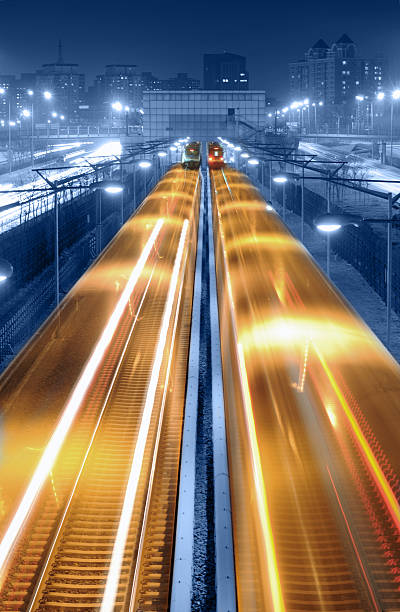 Modern Transportation - XLarge Long exposure photography of high speed train traffic through city at night scene electric train stock pictures, royalty-free photos & images
