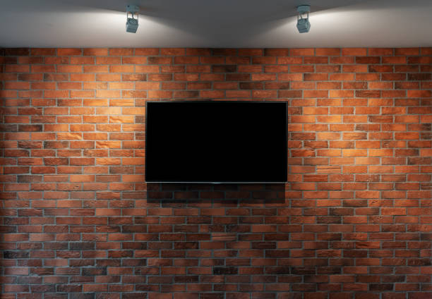 Modern TV with blank black screen, hanging on red brick wall stock photo