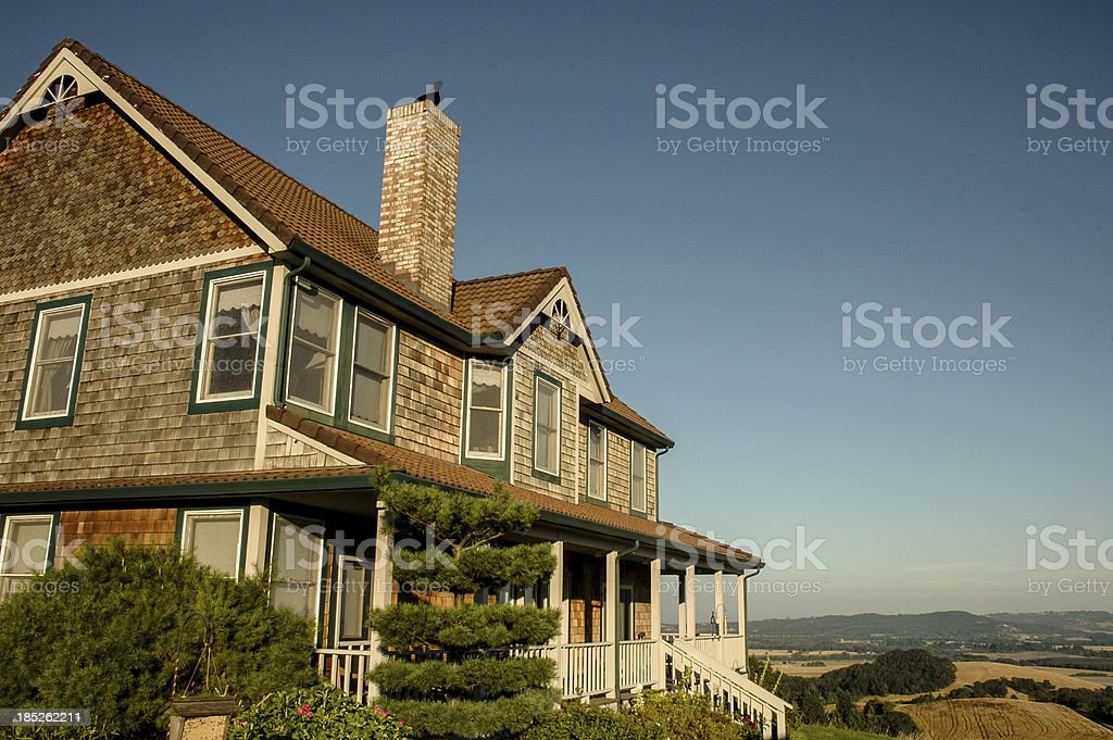 This large house is many shades of brown and white against a...