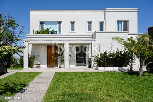 Sunny view of modern two-story home in Buenos Aires with well-tended front yard and walkway leading to entrance.