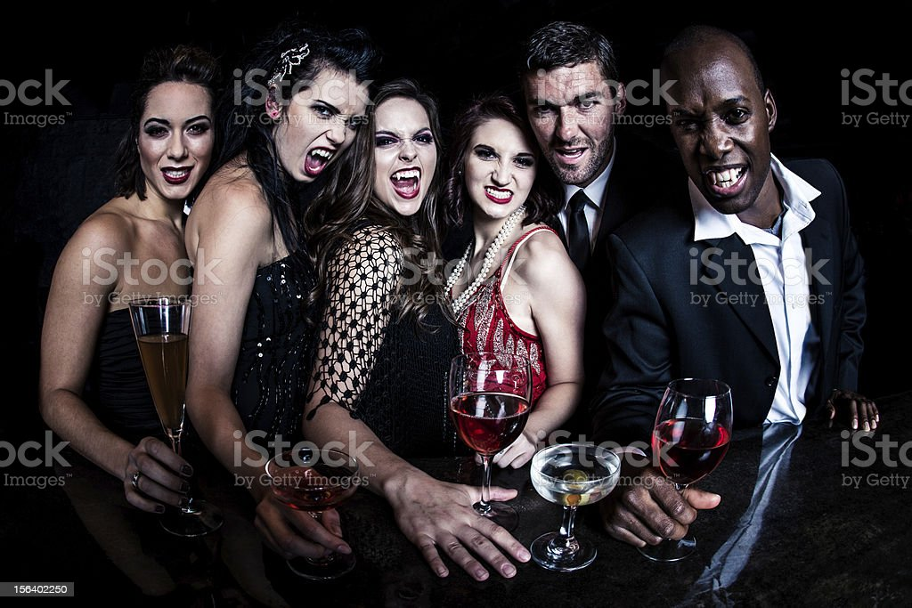 Modern Urban Vampires Modern vampires standing together at the cocktail bar, having drinks, looking towards the bartender, smiling, showing their vampire teeth with a naughty smile. Adult Stock Photo