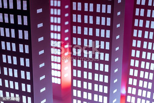 A few cardboard models of high rise buildings with the rows of illuminating windows. The buildings maquettes (floor lamps) stands in different positions relative to each other. Studio shot on red background