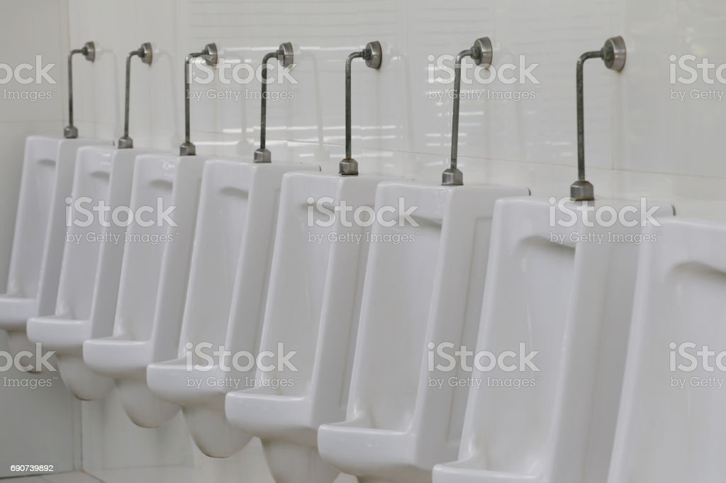 Modern Urinal In Men Bathroom, White Ceramic Urinals For Men In Toilet  Room. Royalty