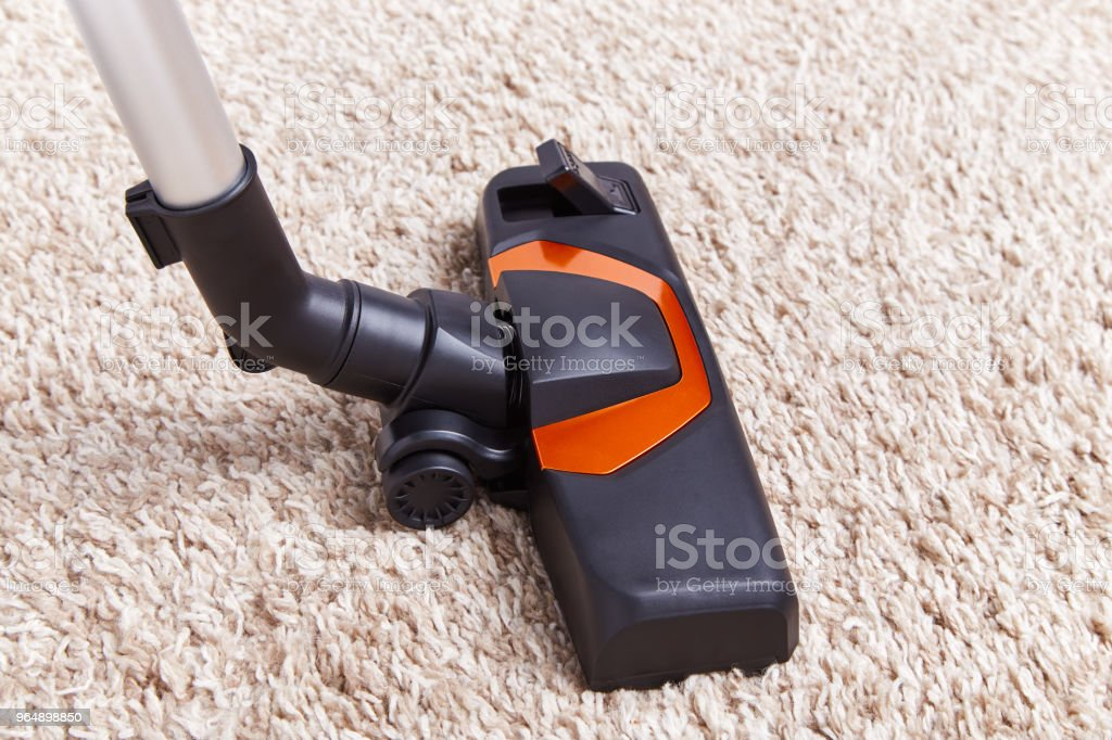 Crop piece of vacuum cleaner in work on top of soft textured carpet...