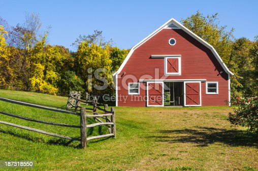 A childs swing hangs from the rafters  in the doorway  of this red barn in central Vermont.
