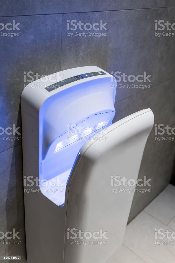 Modern vertical hand dryer in public restroom WC stock photo