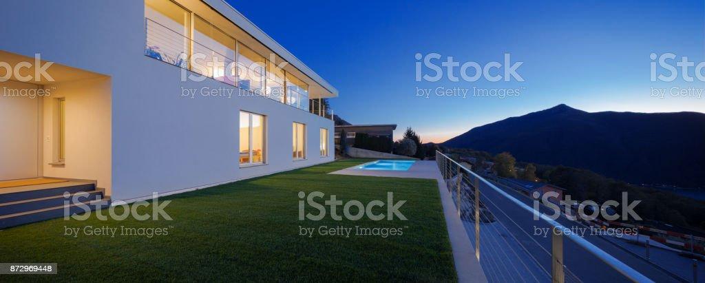 Moderne Villa, außen in der Nacht leuchtet auf – Foto
