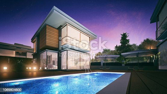 Night view of a modern villa with a swimming pool in front of it.