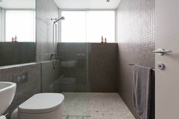 Modern walk in shower with mosaic full height tiles and terrazzo floor stock photo