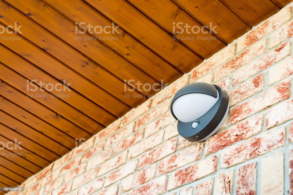 Modern wall lamp with motion and light sensor on the brick wall stock photo