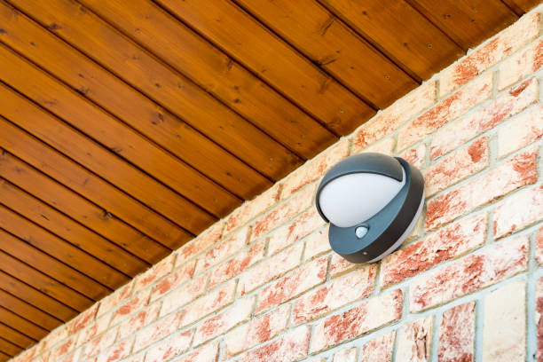 Modern wall lamp with motion and light sensor on the brick wall Modern wall lamp with motion and light sensor on the brick wall - pathway or wall light for modern design building or house - motion activated porch light - part of home security system sensor stock pictures, royalty-free photos & images