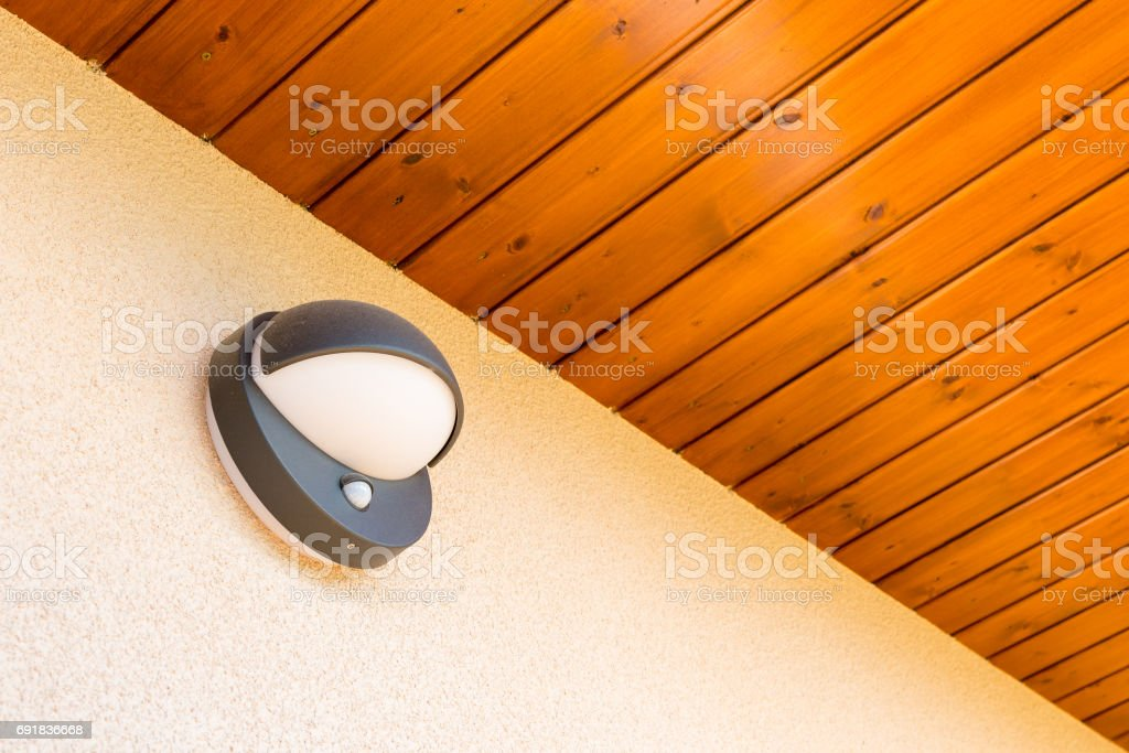 Modern wall lamp with motion and light sensor on the wall stock photo