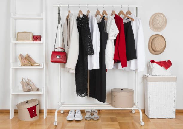 Modern wardrobe interior with different female clothes, hats and shoes stock photo