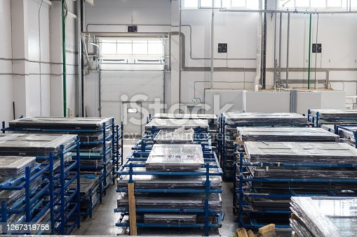 Modern warehouse filled with plastic windows packed in polyethylene. Mid shot