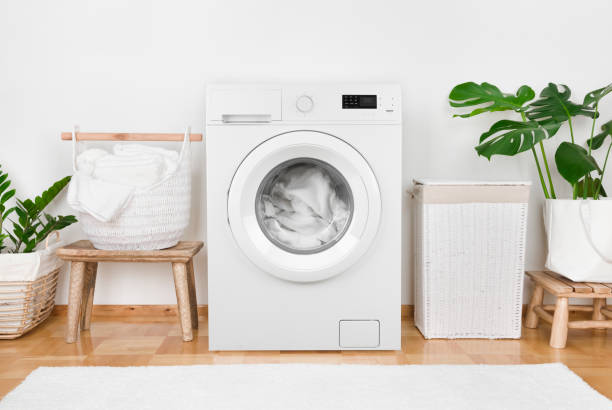 Modern washing machine, laundry in baskets and domestic room interior stock photo