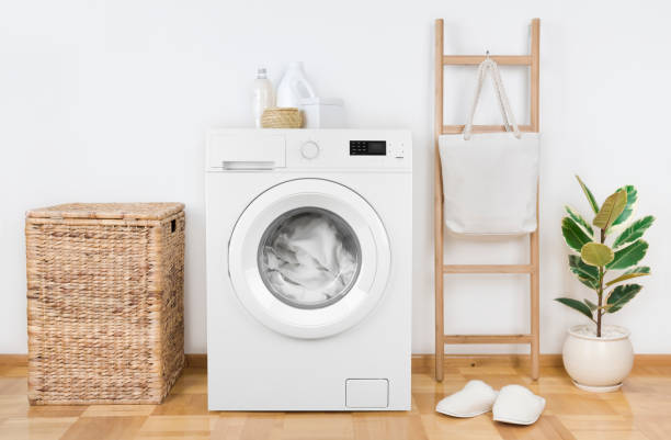 Modern washing machine with basket in laundry room interior stock photo