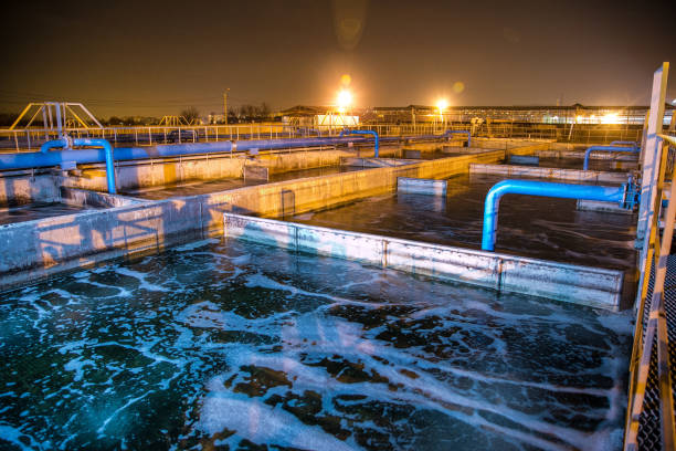Modern wastewater treatment plant of chemical factory at night. Water purification tanks Modern wastewater treatment plant of chemical factory at night. Water purification tanks. sewage stock pictures, royalty-free photos & images