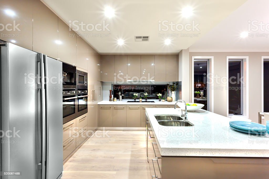 Modern well lit kitchen with stylish new refrigerator stock photo