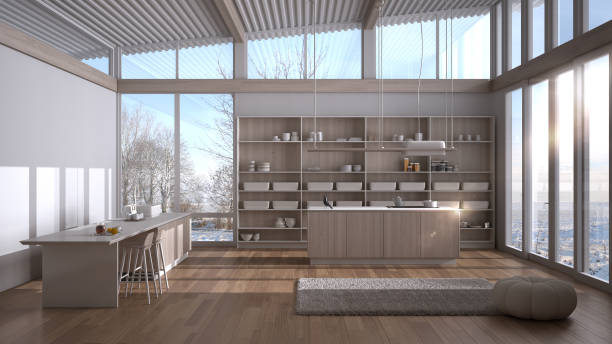 Modern white and wooden kitchen with double island, stools, carpet and accessories, parquet, corrugated sheet roof, panoramic windows on winter view, snow, minimalist interior design stock photo