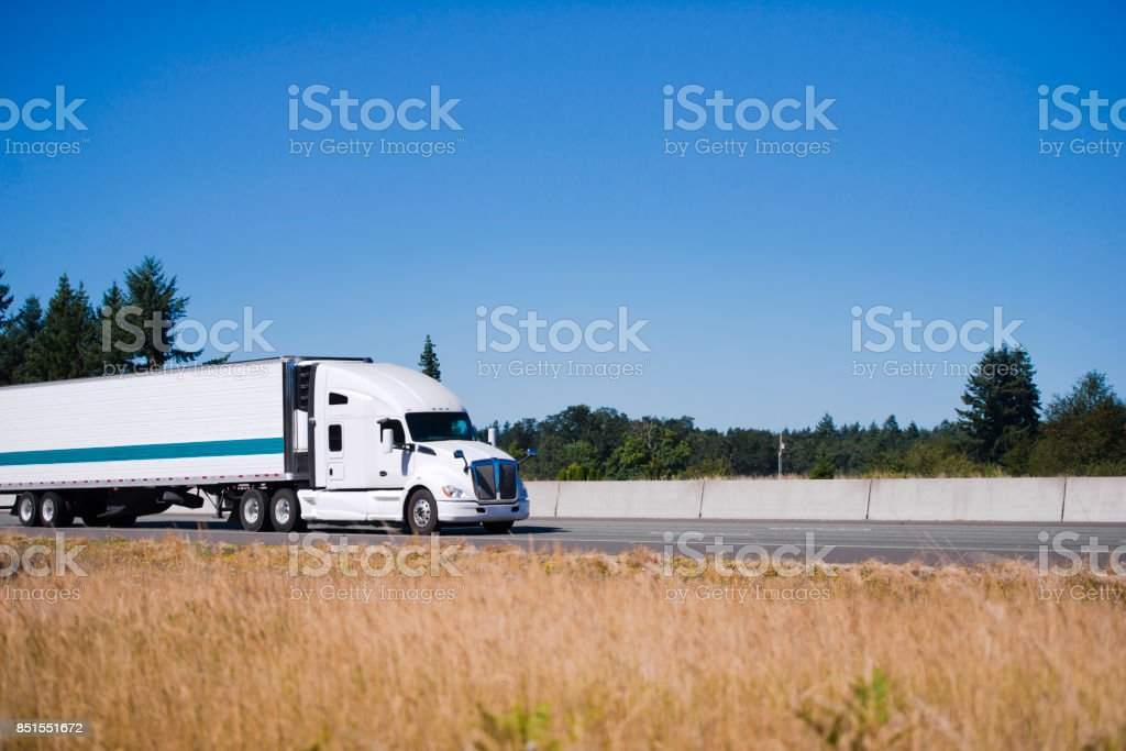 Modern white big rig semi truck with reefer trailer running on highway with yellow grass on shoulder stock photo