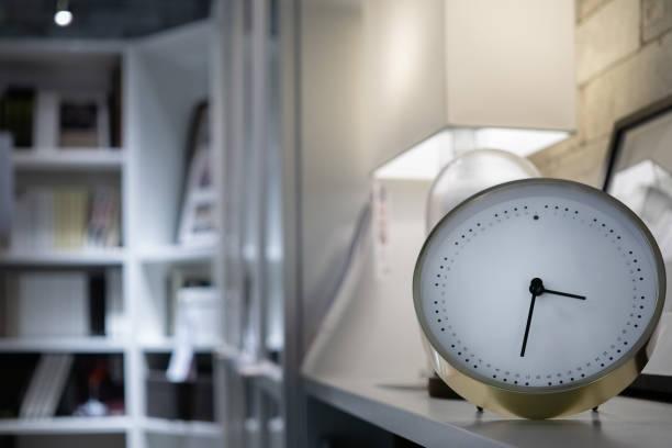 moderne weiße uhr im wohnzimmer mit bücherregalen und lampe - uhrenhalter stock-fotos und bilder