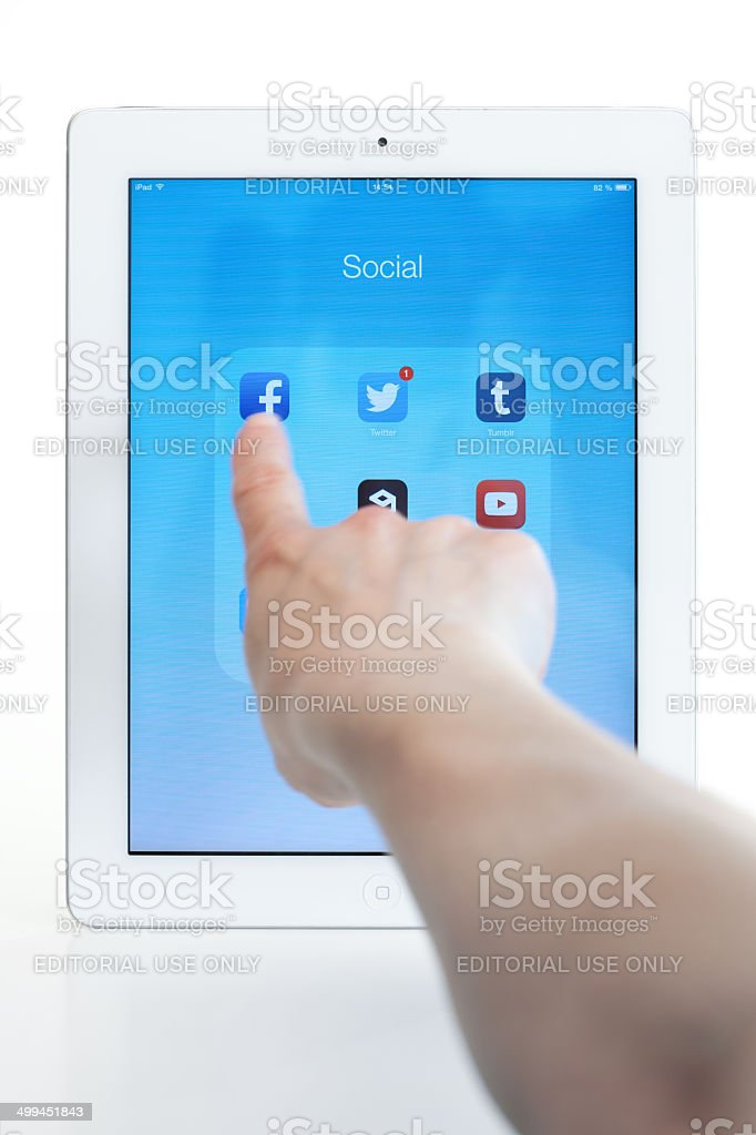 Modern White iPad -Finger touching Facebook app royalty-free stock photo