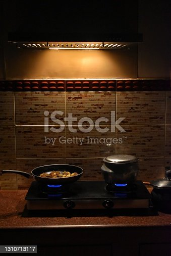 Modern white kitchen with counter and red details, minimalist interior with light in nighttime. Full set of kitchen equipment, pan, pot, electric hob, flipper, vegetable, fruit.