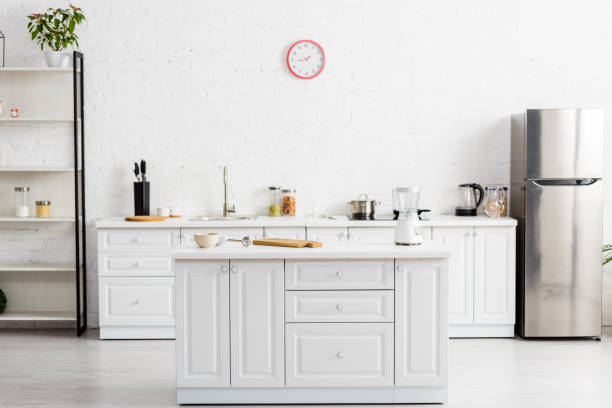 modern white kitchen with table and kitchenware and fridge stock photo