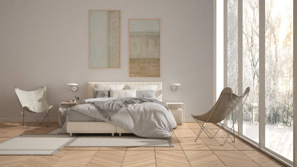 Modern white minimalist bedroom, double bed with pillows and blankets, parquet, bedside tables and carpet. Panoramic window with winter panorama with trees and snow, interior design stock photo