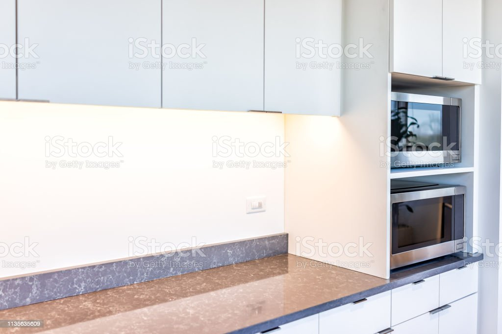 Modern White Minimalist Kitchen Features Cabinets With Granite Countertop And Microwave Toaster With Empty Space In Office Or Home Stock Photo Download Image Now Istock