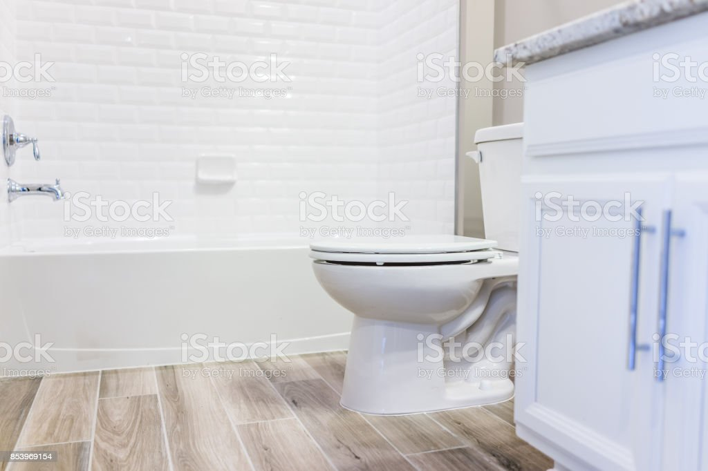 Modern white plain clean toilet bathroom, bathtub with shower tiles and hardwood floors with staging in model staging house, home or apartment stock photo
