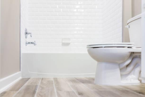banheiro moderno branco liso banheiro limpo com chuveiro azulejos e pisos de madeira do nível do solo - banheiro instalação doméstica - fotografias e filmes do acervo