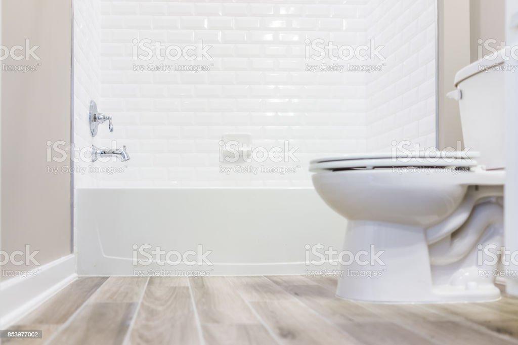 Banheiro moderno branco liso banheiro limpo com chuveiro azulejos e pisos de madeira do nível do solo - foto de acervo