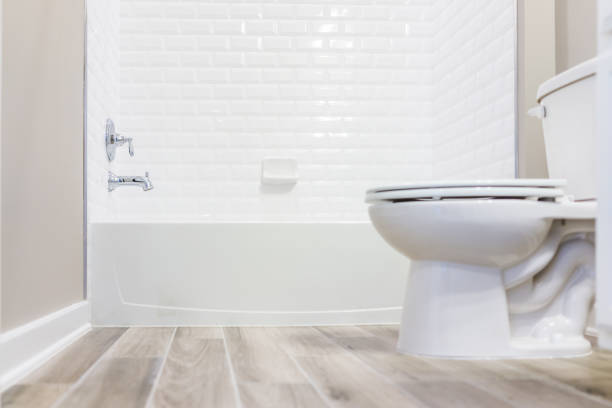 Modern white plain clean toilet bathroom with shower tiles and hardwood floors from ground level stock photo