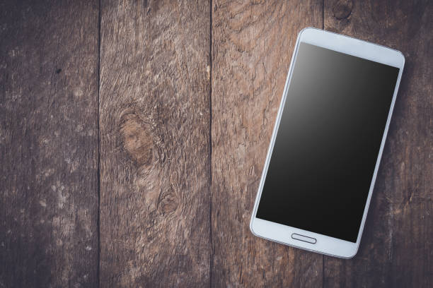 Modern white smart phone on wooden table. stock photo