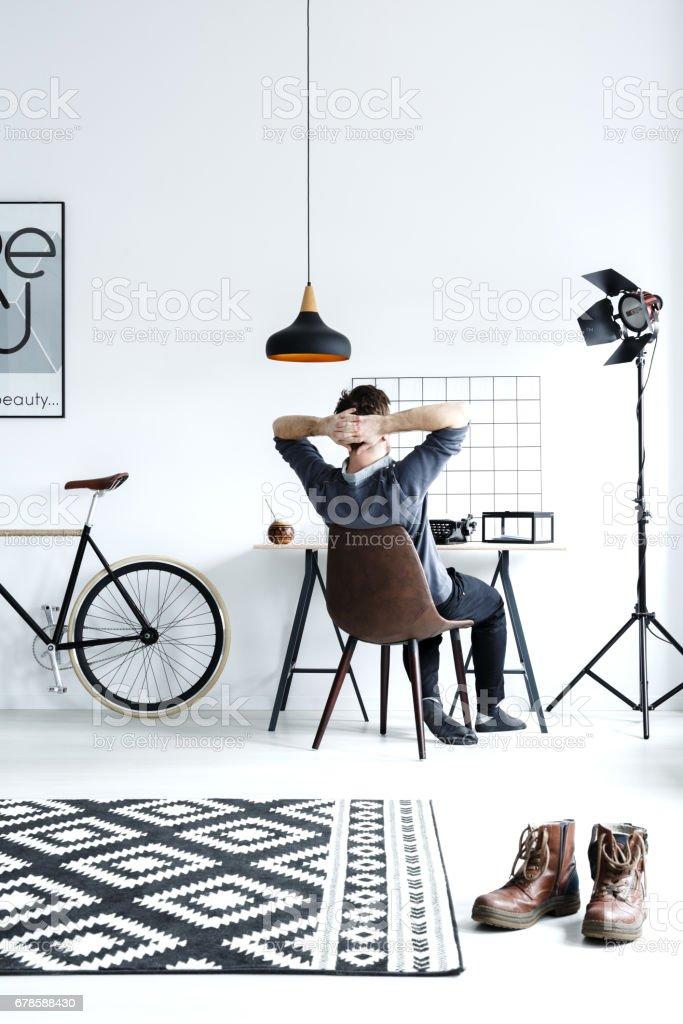 Modern, white studio flat with lamp, desk, chair, and bike