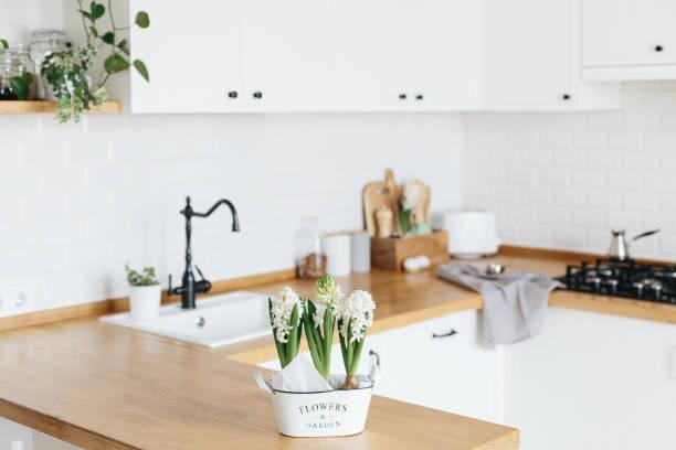 Moderne weiße u-förmige Küche im skandinavischen Stil. Frühlingsdekoration Frühlingsblumen – Foto