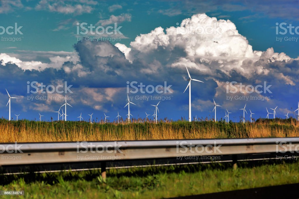 Modern windmill park next to the higway stock photo