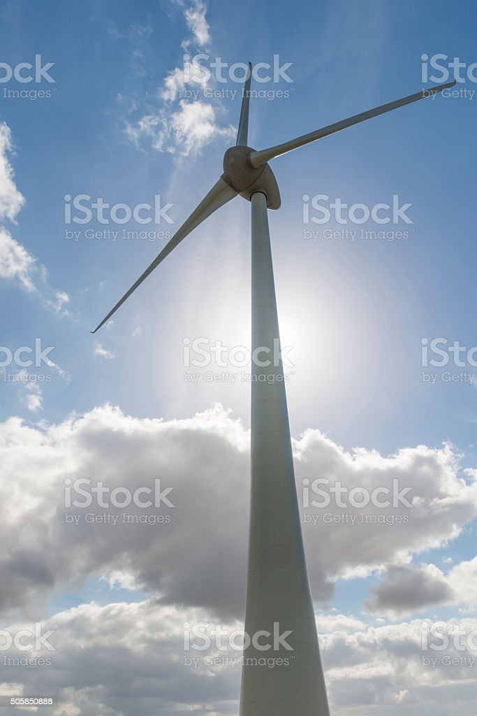 Modern windmill with against light from the Sun. stock photo