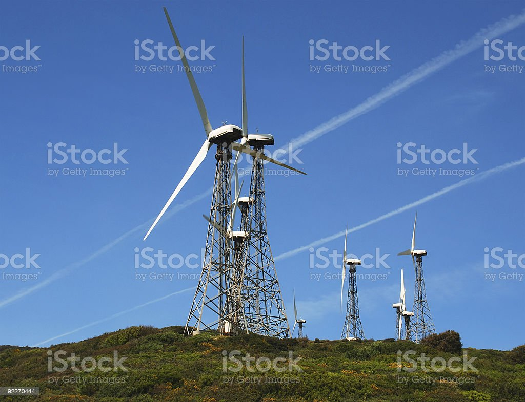 Modern windmills against blue sky with tracks of jetliners royalty-free stock photo
