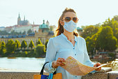 Life during covid-19 pandemic. modern traveller woman in blue blouse with medical mask, sunglasses and map looking into the distance and sightseeing. outdoors in the city.