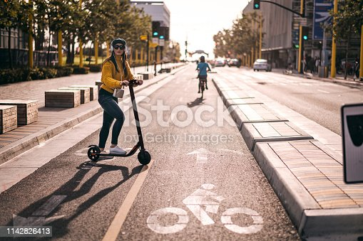 An urban woman listening to music over the headphones looking to join the traffic in the city street downtown.