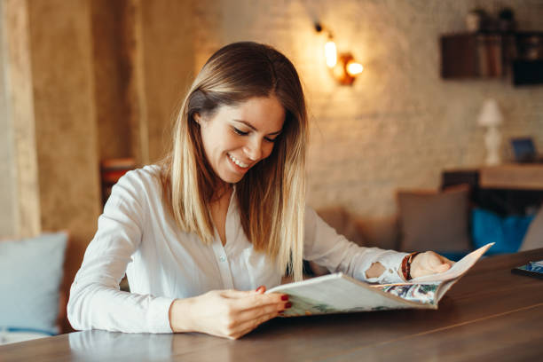 Modern woman reading magazine in cafe stock photo