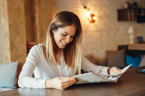 Moderne Frau liest Magazin im café – Foto