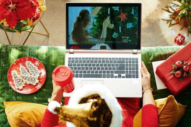 modern woman using internet tv on laptop in room at christmas - christmas movie foto e immagini stock