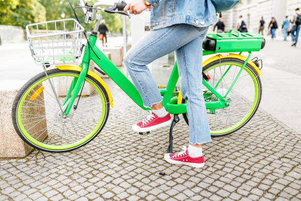 Modern woman wearing casual clothes using rental and sharing system to use Electric bicycle or E-bike on the city street Modern woman wearing casual clothes using rental and sharing system to use Electric bicycle or E-bike on the city street letter e stock pictures, royalty-free photos & images