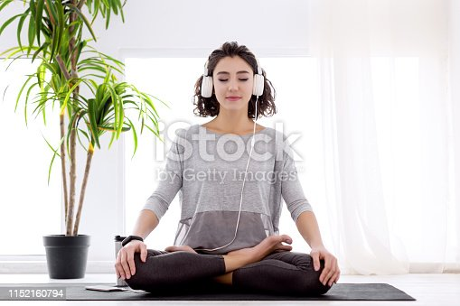 istock Modern woman with headphones sitting in yoga lotus posture 1152160794